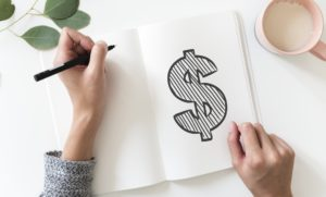 A woman drawing a dollar sign in a notebook.